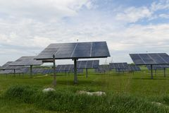 De zonnepanelen op een grasrijk gebied tonen duurzame energie aan Royalty-vrije Stock Foto