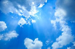 De zonnestraal glanst door de wolk op de blauwe hemel stock fotografie