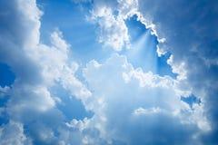 De zonnestraal glanst door de wolk op de blauwe hemel royalty-vrije stock foto's
