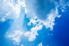 De zonnestraal glanst door de wolk op de blauwe hemel royalty-vrije stock afbeelding