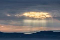 De zonnestraal glanst door wolken over de bergen en een overzees van mist stock foto