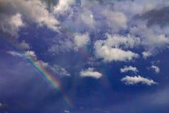 De zonnige dag op de kust Talrijke geïsoleerde wolken liet de hemel zien De regenboog overheerst de hemel royalty-vrije stock afbeelding