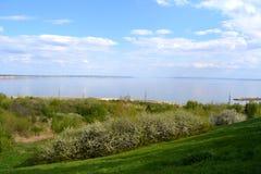 De zonnige dag van de lente Landschap met rivier en bloeiende bomen op grasheuvel Royalty-vrije Stock Afbeelding