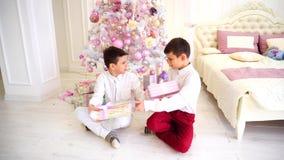 De zonnige ochtend na Kerstmis en uitwisseling van stelt door siblings voor die op vloer in slaapkamer met Kerstboom zitten stock footage
