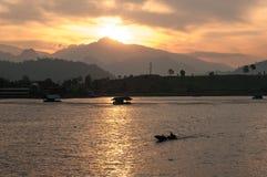 De zonreeksen achter de berg, die omhoog de laatste stralen van een vissersboot aansteken, die in een tropische baai wordt verank Royalty-vrije Stock Fotografie