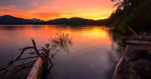 De zonsondergang denkt in Meer met Bergen in Afstand na Stock Foto's