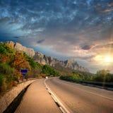 De zonsondergang en de weg van de berg stock afbeelding