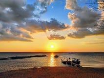 De zonsondergang en de vissers die naar huis gaan royalty-vrije stock afbeeldingen