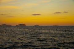 In de zonsondergang leidden de machtige marineschepen voor de haven stock afbeeldingen