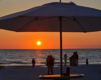 De zonsondergang met het silhouet van een paraplu en mensen op het strand Dit is bij Indisch Rotsenstrand, Golf van Mexico, Flori royalty-vrije stock foto's