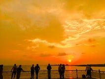 De zonsondergang met ontspant mensen stock afbeeldingen