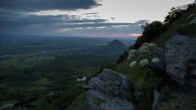 De zonsondergang op de helling van Onderstel Beshtau en komt langzaam nacht, de lichten omhoog van het stadslicht De lichte lucht stock video
