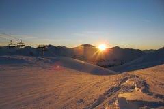 De zonsondergang over een sneeuw behandelde alpiene bergketen Royalty-vrije Stock Foto's