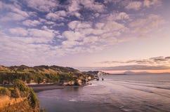 De zonsondergang over overzeese kustrotsen en zet Taranaki, Nieuw Zeeland op Royalty-vrije Stock Foto