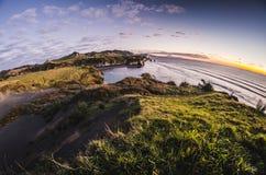 De zonsondergang over overzeese kustrotsen en zet Taranaki, Nieuw Zeeland op Royalty-vrije Stock Foto's