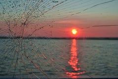 De zonsondergang in rivier werpt het gebroken glas royalty-vrije stock foto