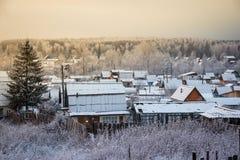 De zonsondergang van de avondwinter over huizen in de voorsteden op horizont De winter Stock Afbeelding