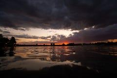 De zonsondergang van Boekarest in Herastrau-park, onweerswolken met meerbezinning Roemenië royalty-vrije stock afbeelding