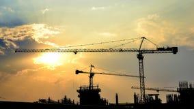 De zonsondergang van de tijdtijdspanne en silhouetkraan in bouwwerf stock video