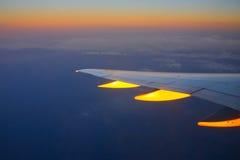 De zonsondergang van de vlucht en gouden wolken Stock Afbeelding