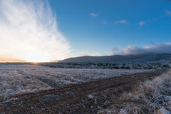 De zonsondergang van de wintergebieden met wolken die zich door wind bewegen Stock Foto
