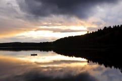 De zonsondergang van het meer over bos royalty-vrije stock afbeelding