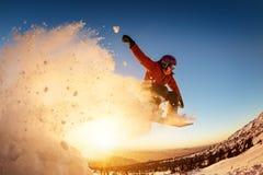 De zonsondergang van Snowboardersprongen met sneeuwstof Stock Foto's