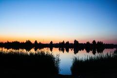 De zonsondergang van de zomer over het meer stock afbeelding
