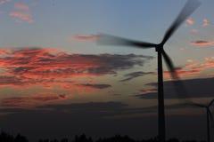 In de zonsonderganggloed op de achtergrond van een windturbine in de machtsgeneratie Royalty-vrije Stock Foto