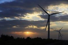 In de zonsonderganggloed op de achtergrond van een windturbine in de machtsgeneratie Stock Foto