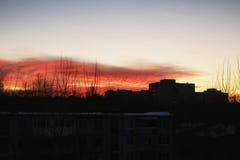 De zonsonderganghemel speelt silhouetten van gebouwen mee stock fotografie