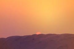 De zonsonderganglandschap van de zomer De het plaatsen zon en de kleurrijke hemel boven het zand Stock Fotografie
