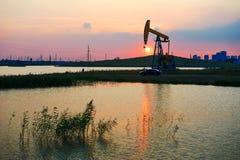 De zonsondergangoever van het meer van de olie pompende machine Stock Foto's