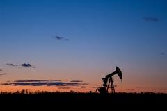 De zonsondergangsilhouet van de oliebron pumpjack royalty-vrije stock afbeeldingen
