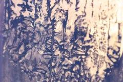 De zonsondergangzon glanst door het bevroren venster De patronen van het ijs op glas royalty-vrije stock foto's