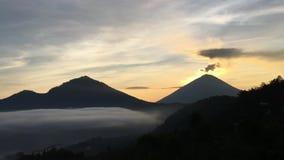 De zonsopgang boven Meer Batur behandelde met Wolken en zet Agung Erupting Smoke op - dat vanaf Bovenkant van Onderstel Batur in  stock footage