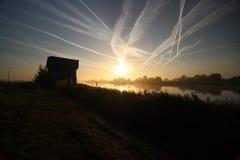 De zonsopgang met gekleurde vliegtuigen sleept, mist op de weiden en bij Rivier Hollandsche IJssel stock afbeelding