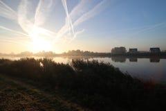 De zonsopgang met gekleurde vliegtuigen sleept, mist op de weiden en bij Rivier Hollandsche IJssel royalty-vrije stock foto