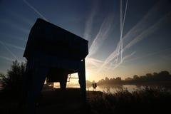 De zonsopgang met gekleurde vliegtuigen sleept, mist op de weiden en bij Rivier Hollandsche IJssel stock fotografie