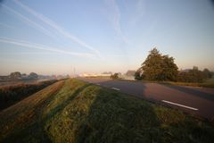 De zonsopgang met gekleurde vliegtuigen sleept, mist op de weiden en bij Rivier Hollandsche IJssel stock foto's