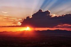De zonstralen glanzen achter een cumuluswolk bij zonsondergang Royalty-vrije Stock Foto's