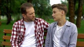 De zoon deelt geheim met vader, op vertrouwen-gebaseerde warme relaties, tiener omhoog het brengen royalty-vrije stock foto