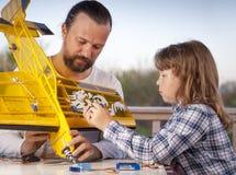 De zoon en het vader gemaakte eigengemaakte radio-gecontroleerde modelvliegtuigenvliegtuig zijn hand - gemaakt niet auteursrecht stock foto