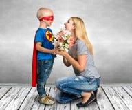 De zoon in het kostuum van een superhero geeft zijn moeder een boeket van bloemen royalty-vrije stock afbeeldingen
