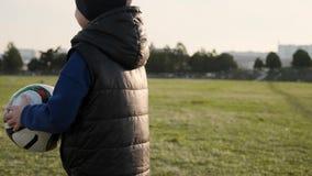 De zoon neemt de bal en schopt het aan zijn papa speelvoetbal in vroege de lente langzame motie stock videobeelden