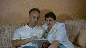 De zoon onderwijst een bejaarde moeder om de tablet te gebruiken stock footage
