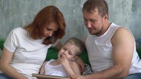De zoon toont het interesseren in de tablet aan ouders Mensen met technologie stock video