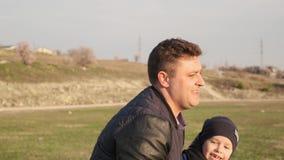 De zoon valt op gras en lacht tijdens het voetbalspel met zijn grappige papa langzame motie stock video