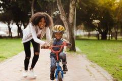 De zoon van het moederonderwijs om fiets te berijden stock afbeeldingen