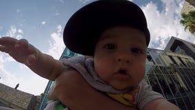 De zoon van de vaderholding in een GLB ter beschikking op de straat stock footage